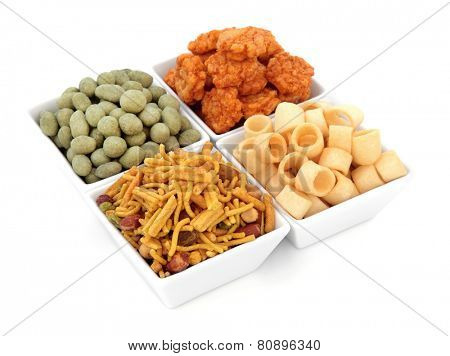 Savory snack party food selection in square porcelain bowls over white background.