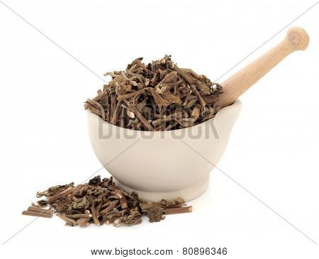 Korean mint herb used in chinese herbal medicine in a stone mortar with pestle over white background. Huo xiang.