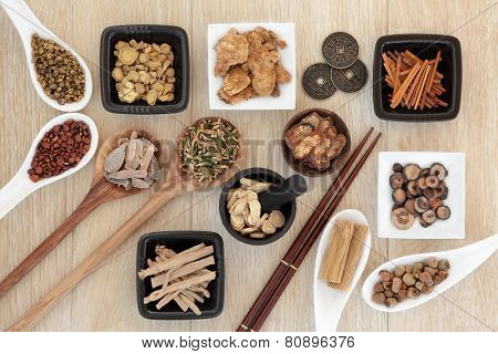 Chinese herbal medicine selection with I ching coins, mortar with pestle and chopsticks over light oak background.