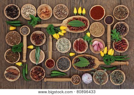 Chlli spice and herb ingredients in wooden bowls, spoons and loose over old oak background.