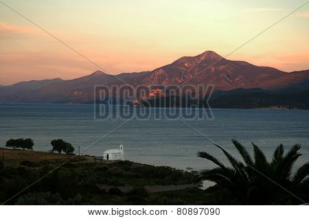 A small white church on the Aegean coast at sunset