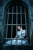 stock photo of gothic female  - Woman in victorian dress imprisoned in a dungeon - JPG