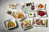 picture of ouzo  - variety of greek appetizers on white wood - JPG