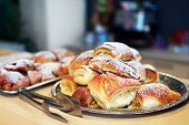 stock photo of tong  - Buns with powdered sugar on a metal tray and kitchen tongs - JPG