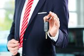 pic of car key  - Seller or car salesman in car dealership with key presenting his new and used cars in the showroom - JPG