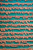 stock photo of mantra  - Classical wall in Nepal Kathmandu with mantras written on it in gold letters on a green background. Everything is made in stone