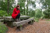 stock photo of overcoats  - Young woman feeling depressed sitting on a stone table and bench on a forest wearing a red overcoat during winter  - JPG
