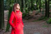 stock photo of overcoats  - Woman enjoying the warmth of the winter sunlight on a forest wearing a red overcoat - JPG