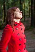 foto of overcoats  - Woman enjoying the warmth of the winter sunlight on a forest wearing a red overcoat - JPG