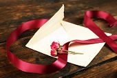 Постер, плакат: Envelope with love letter vinous ribbon and dried rose on rustic wooden table background