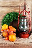 foto of kerosene lamp  - Kerosene lamp with wreath and oranges in wicker basket on wooden planks background - JPG