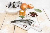 foto of caught  - Freshly caught herring with spices on the wooden background - JPG