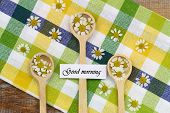 foto of chamomile  - Good morning card with fresh chamomile flowers on wooden spoons on checkered cloth - JPG