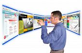 image of web template  - A business man is searching and pointing at an internet website and there are many web choices - JPG