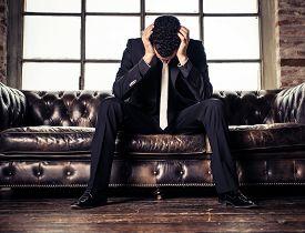foto of fail job  - Depressed business man sitting on sofa  - JPG