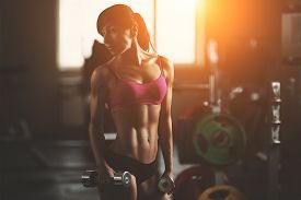 image of sportswear  - Brutal athletic woman pumping up muscles with dumbbells - JPG