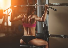 stock photo of slim model  - Brutal athletic woman pumping up muscles with dumbbells - JPG
