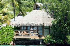 foto of toples  - man and woman at a tropical resort bungalow - JPG