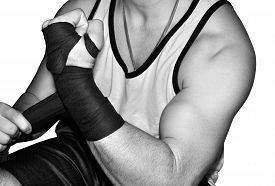 pic of grayscale  - Grayscale of a muscled fighter wrapping one of his wrists before a match - JPG
