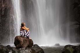 stock photo of breathing exercise  - woman meditating doing yoga between beautiful waterfalls - JPG