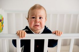 image of cry  - The baby cries and calls mom from a bed - JPG