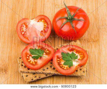 Wheat Crisp Bread And Tomato On Bamboo Board