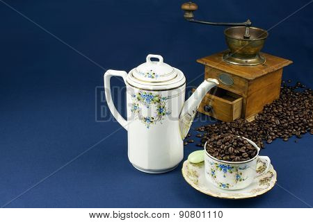 coffee mug on the table with a blue tablecloth, poured out coffee beans