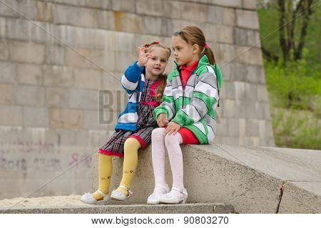 Girl Shows Something Other Girl, Sitting On A Granite Ramp