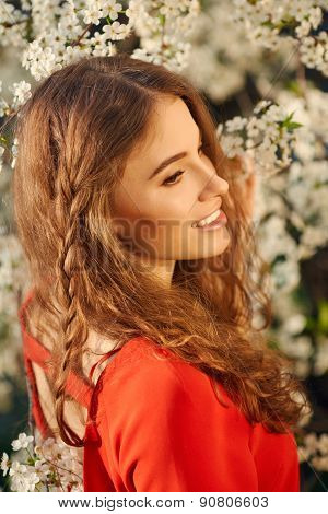 Young Woman In Red Dress Enjoying Smell Of Blooming Tree