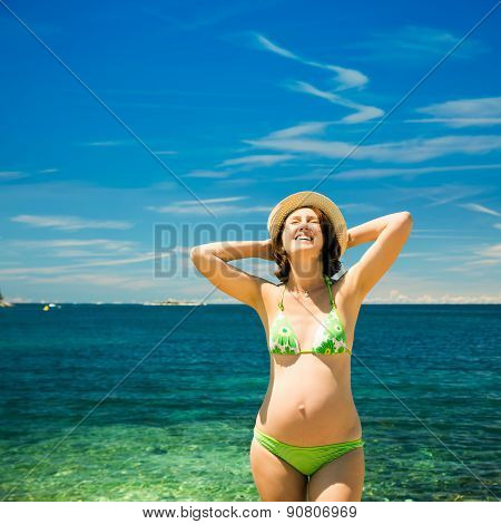 Happy Pregnant Woman Sunbathing at the Sea
