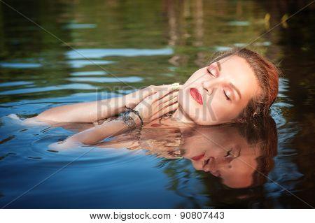 Beautiful Young Woman Lying In The Water