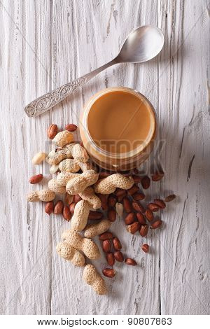 Peanut Butter In A Glass Jar And Nuts Close-up Vertical Top View
