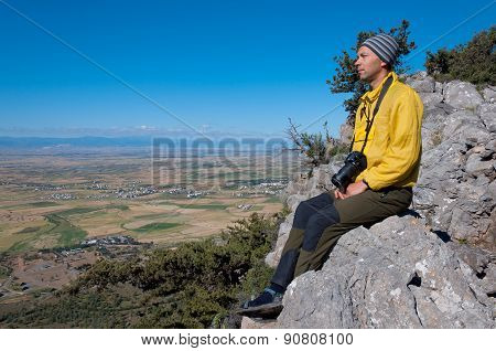 Young tourist with a camera resting on top overlooking the valley