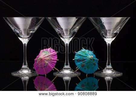 Three Empty Glasses Of Champagne With Paper Umbrellas