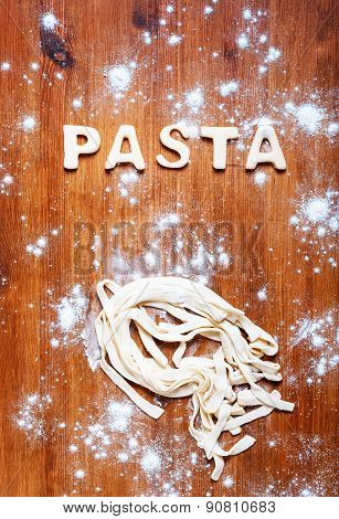 Letters of dough and pasta on the wooden table