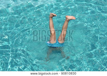 boy sticks his legs out from the water of pool