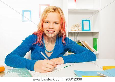 Happy girl smile, write in textbook doing homework