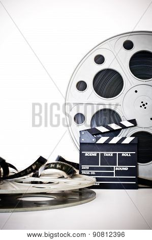Movie Clapper And Vintage 35 Mm Film Cinema Reel On White