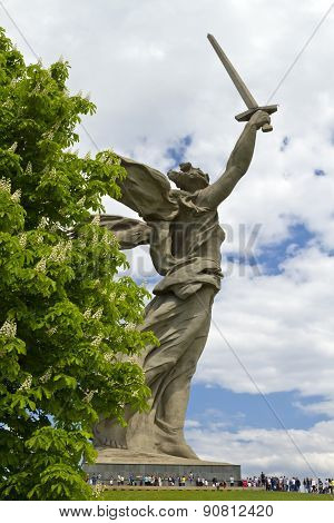 The Sculpture Of The Motherland Is Calling Mamayev Kurgan On The Background Of A Flowering Chestnut