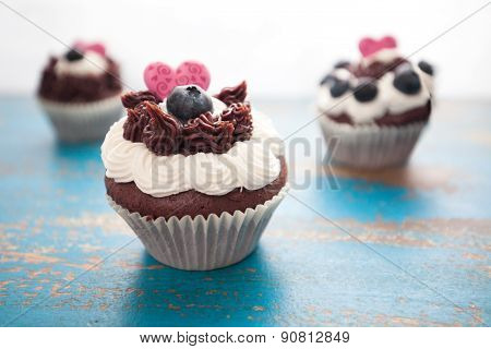 Decorated Chocolate Cupcakes On Rustic Blue Table