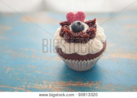 Decorated Cupcake On Rustic Blue Table Top