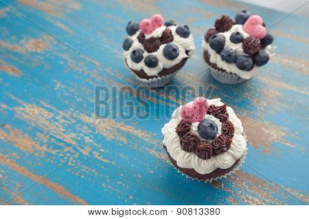 Three Decorated Cupcakes On Rustic Blue Table Top