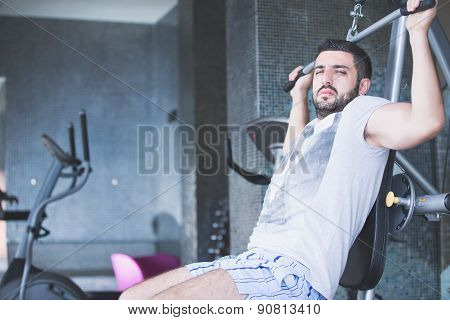 Man using pull down machine in gymnasium.Handsome muscular man exercising on pull down machine