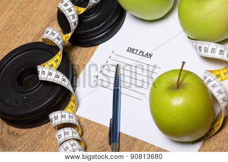 Sheet Of Paper With Diet Plan, Apples And Dumbbell On Wooden Table