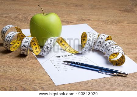 Paper With Diet Plan, Apple And Measure Tape On Table