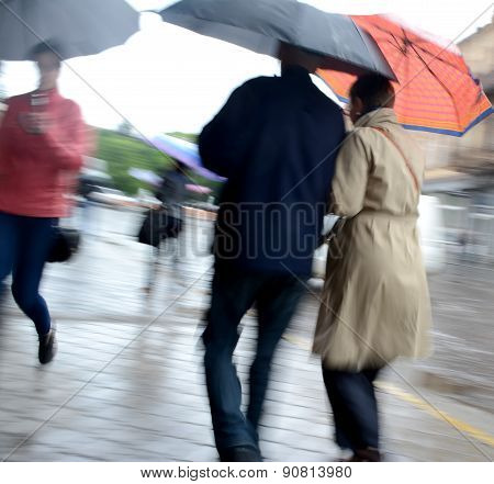 Women Walking Down The Street On A Rainy Day
