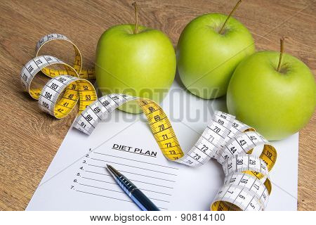 Diet Concept - Close Up Of Paper With Diet Plan, Apples And Measure Tape On Table