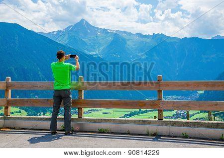 Male tourist taking photo of alpine landscape
