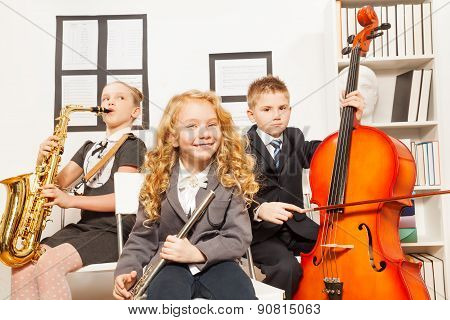 Happy children play musical instruments together
