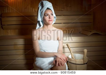 Pretty young  woman sitting relaxed in a wooden sauna.Young woman in white towel sitting in Finnish